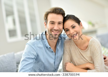 Young smiling couple sitting in sofa at home - stock photo