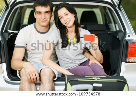Young smiling couple sitting in the opened car bloom holding empty credit cards - stock photo