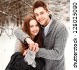 Young smiling couple smiling and posing outdoor in winter forest - stock photo