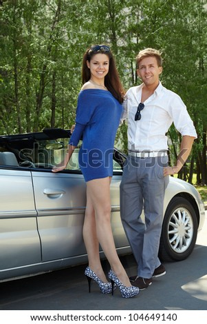 Young smiling couple stands near cabriolet and looks into camera
