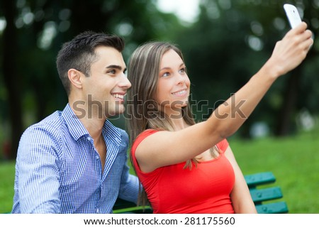 Young smiling couple taking a selfie portrait - stock photo