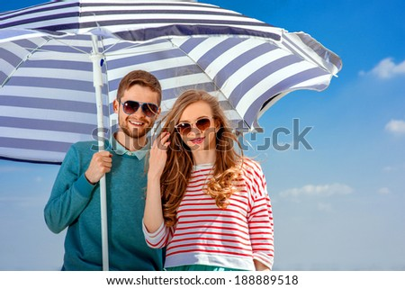 Young smiling couple under the umbrella on blue sky background  - stock photo