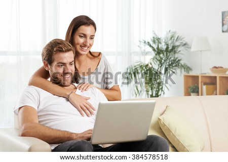 Young smiling couple watching movie on laptop at home