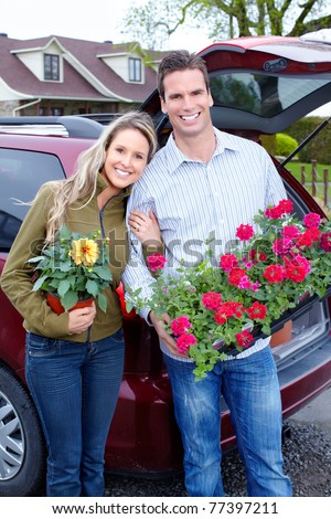 Young smiling couple with flowers near home.