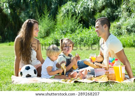 Young smiling couple with little daughters having holiday with picnic