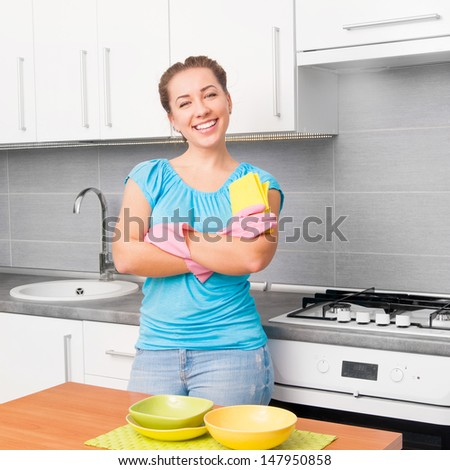 young smiling cute woman cleans the kitchen - stock photo