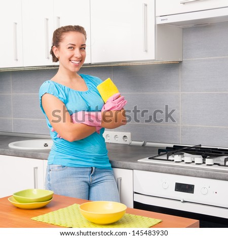 young smiling cute woman cleans the kitchen at  home - stock photo