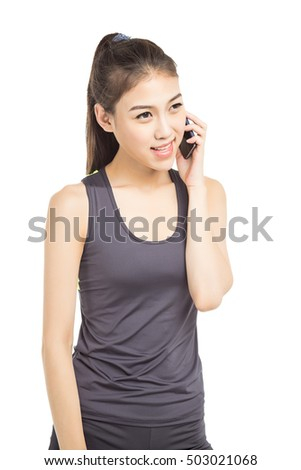 Young smiling fair-haired sportswoman talks by mobile phone against big sports hall.