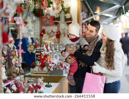 Young smiling family of three at Christmas market. Shallow depth of focus  - stock photo