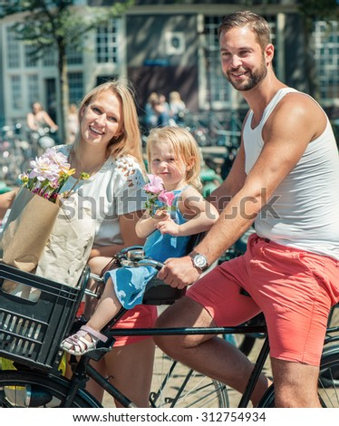 Young smiling family riding bicycles at the streets of Amsterdam - stock photo