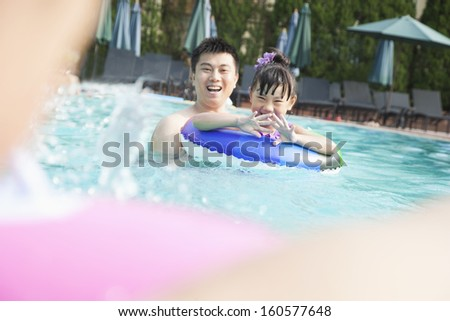 Young smiling family splashing and playing in pool - stock photo