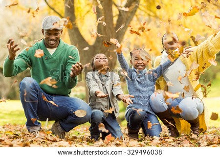 Young smiling family throwing leaves around on an autumns day - stock photo