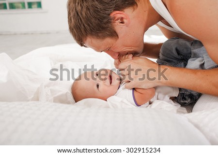 Young smiling father with his nine months old son on the bed at home on white home background - stock photo