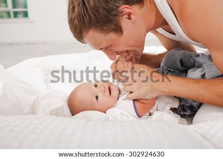Young smiling father with his nine months old son on the bed at home on white home background