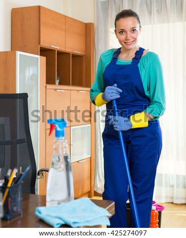 Young smiling female cleaner in uniform washing the floor at office