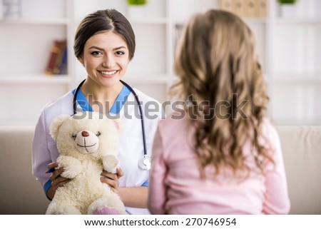 Young smiling female doctor with teddy bear and little girl.