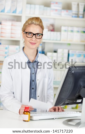 Young smiling female pharmacist with prescription at the drugstore - stock photo