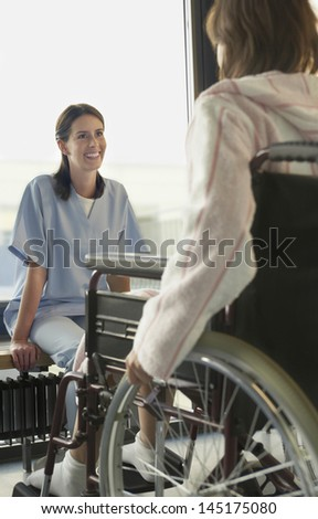 Young smiling female physician listening to patient in wheelchair - stock photo