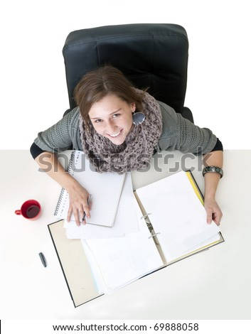 Young smiling female student looking up from the notes on her desk seen from above