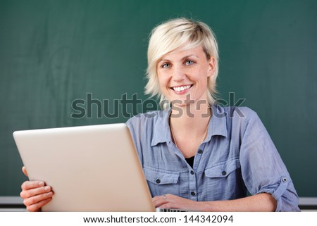 Young smiling female teacher with laptop sitting at school table - stock photo