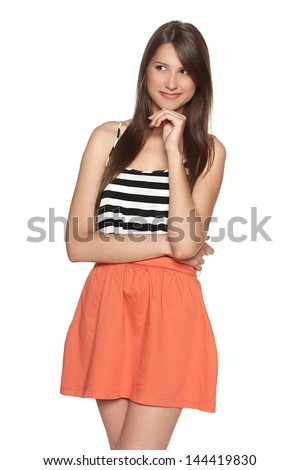 Young smiling female with hand on chin looking to the side, against white background - stock photo