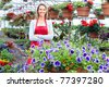Young smiling florist working in the greenhouse. - stock photo