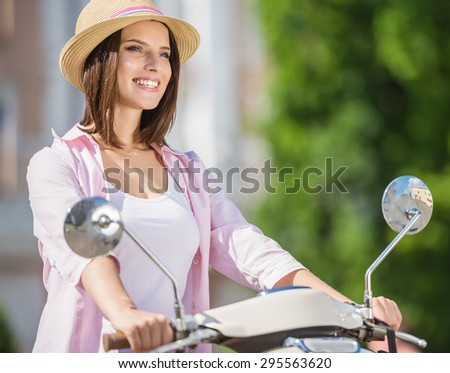 Young smiling girl dressed casual driving scooter in european city. - stock photo
