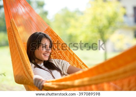 Young smiling girl enjoy in hammock in woods - stock photo