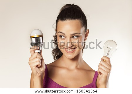 young smiling girl holds in her hands the old and the new generation of light bulbs - stock photo