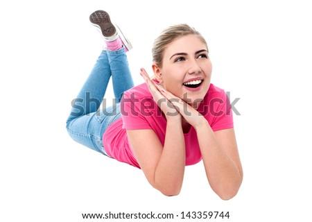 Young smiling girl lying on floor, studio shot - stock photo