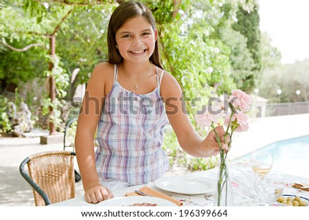 Young smiling girl preparing an outdoors lunch table with fresh Spanish tapas food in a summer holiday villa green garden, arranging carnations flowers enjoying a vacation. Outdoors eating lifestyle.