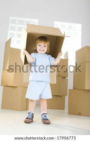 Young smiling girl standing between cadboard boxes. She's holding one box over head. She's looking at camera.