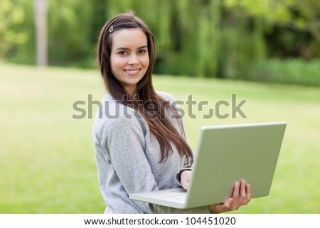 Young smiling girl standing upright in a parkland while working on her laptop