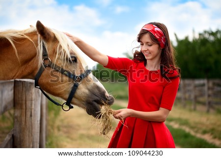 young smiling girl stroked  her horse, friendship