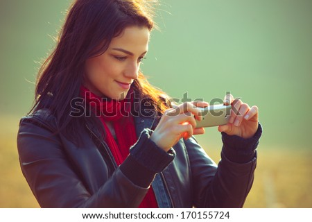 young smiling girl  take photo with mobile phone outdoor shot - stock photo