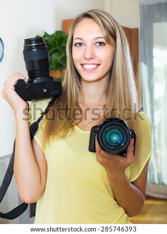 Young smiling girl testing  professional cameras  indoor