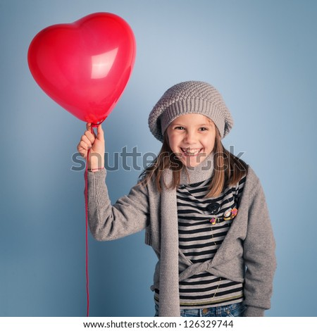 Young smiling girl with red heart balloon on blue background. - stock photo