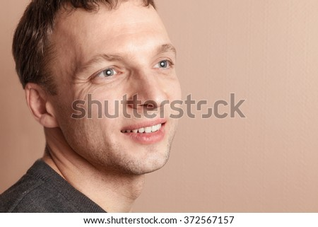 Young smiling handsome Caucasian man, close-up studio portrait over gray wall background