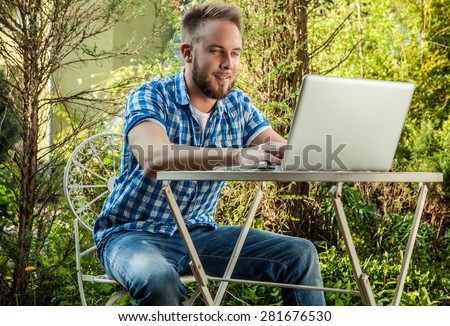 Young smiling handsome man in casual clothes work at an iron table with computer against country garden.