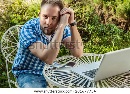 Young smiling handsome man in casual clothes work at an iron table with computer against country garden. - stock photo
