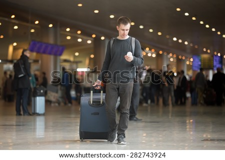 Young smiling handsome man in 20s walking in modern airport terminal, using smart phone app in public wifi area, texting, travelling with luggage bag, wearing casual style clothes - stock photo
