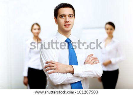 Young smiling happy businessman at work in office - stock photo