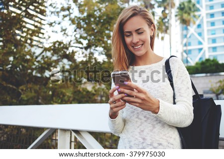 Young smiling hipster girl pleasantly read text message on her cell telephone while standing on the street, cheerful pretty woman chatting on smart phone with friend during walking in the fresh air  - stock photo
