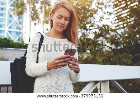 Young smiling hipster girl pleasantly read text message on her cell telephone while standing on the street, cheerful pretty woman chatting on smart phone with friend during walking in the fresh air