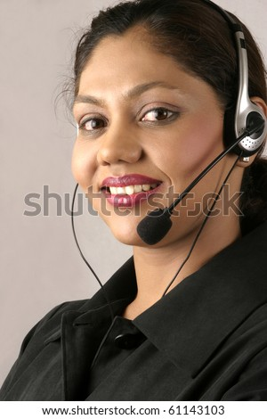 Young smiling Indian customer care assistant at call center - stock photo