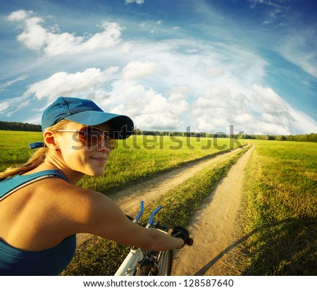 Young smiling lady cycling on a countryside road at summer sunny day