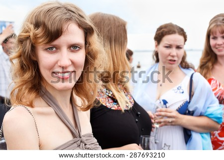 Young smiling lady looking at camera while friends talking together, party