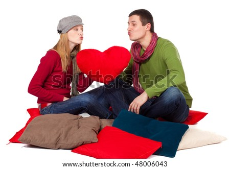 Young smiling loving couple sitting on pillows with big red heart
