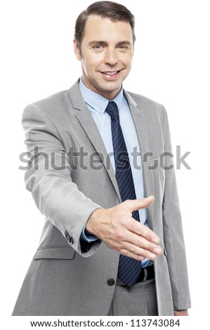 Young smiling male executive welcoming you with a handshake isolated against white background - stock photo