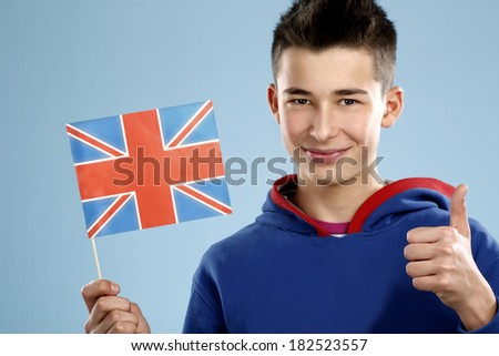 young smiling male student teenager holding a flag on blue